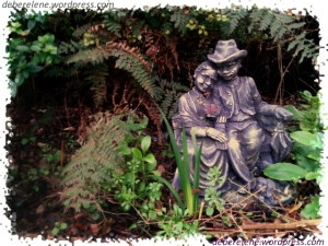 Garden ornament of an elderly couple cuddling on a garden bench