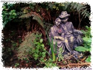 Garden ornament of an elderly couple cuddling on a garden bench